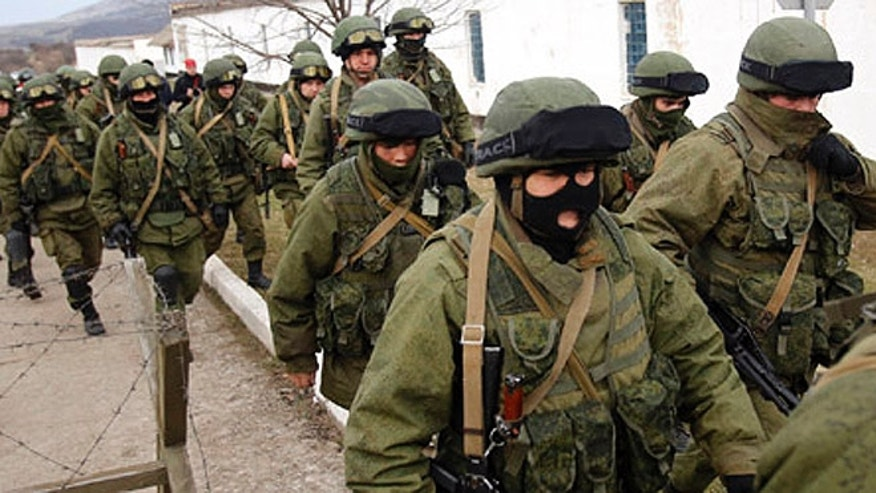 Ukrainian soldiers (left) and unidentified armed men (right) at the entrance of a base infantry Perevalne, Ukraine.  (AP Photo/Darko Vojinovic)