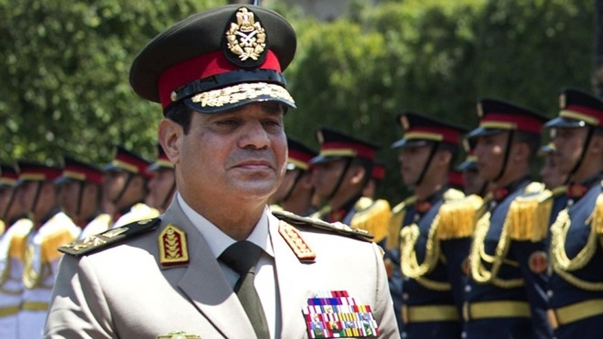 "April 24, 2013: In this file photo, Egyptian Defense Minister Gen. Abdel-Fattah el-Sissi reviews honor guards during an arrival ceremony for his U.S. counterpart at the Ministry of Defense in Cairo. Egypt's military chief says he ""can't turn his back"" if the majority of Egyptians want him to run for president."