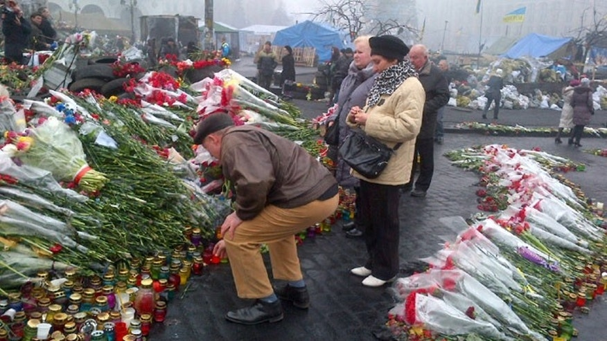 People still pile fresh flowers on the memorials in Kiev's Independence Square, although an uneasiness now hangs in the smoky air, (Fox News)