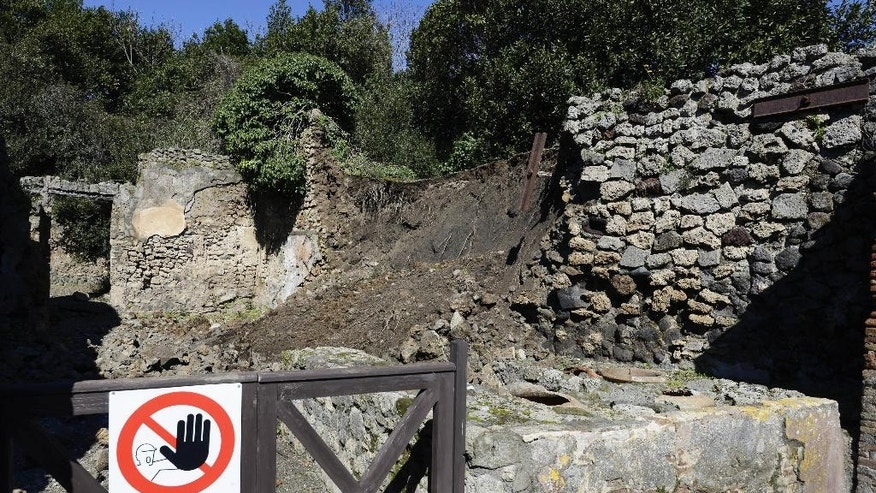 Bricks and rocks are seen on the ground after a section of wall around an ancient shop collapsed in Pompeii as a consequence of a rainstorm, Monday, March 3, 2014. Pompeii's archaeological office said Monday a section of the recently restored wall had collapsed. The damage is in an area long closed to the public, at the edge of the excavations of the ancient Roman city. Officials said inadequate drainage in the unexcavated part is particularly worrisome. Rains lashing the Naples area recently were also blamed for damage discovered Sunday in other parts of Pompeii. (AP Photo/Salvatore Laporta)