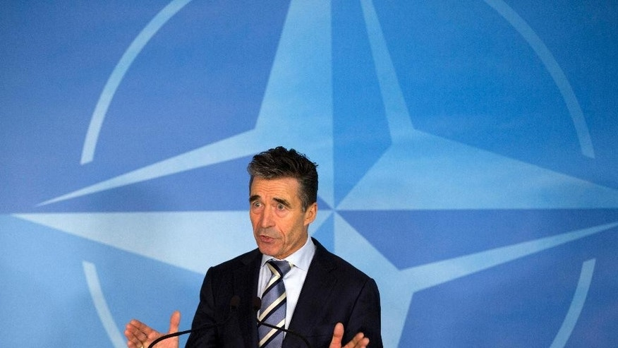 NATO Secretary General Anders Fogh Rasmussen walks away with his papers after speaking at a media conference at NATO headquarters in Brussels on Sunday, March 2, 2014. NATO called for emergency talks on Sunday regarding the escalating crisis in Ukraine. (AP Photo/Virginia Mayo)