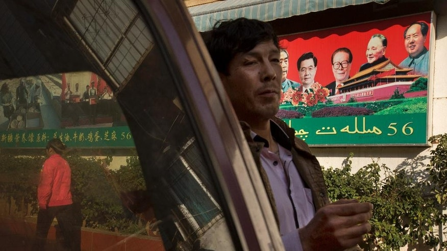 In this Monday, March 3, 2014 photo, a Uighur man walks past a propaganda poster, partially in Uighur language, urging for ethnic unity in a community shared by both ethnic Uighur and Han Chinese residents in Kunming, in western China's Yunnan province. China said the vicious slashing spree Saturday that killed 29 people in the southern city was the work of separatists linked to international terrorism, but the assailants' homespun methods and low-tech weapons - nothing more than long knives - have led some analysts to suspect they didn't get outside help.  (AP Photo/Alexander F. Yuan)