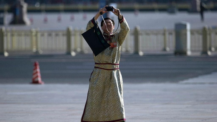 A delegate in ethnic minority costume takes a photo as he arrives at the Great Hall of the People to attend sessions of National People's Congress and Chinese People's Political Consultative Conference in Beijing, China, Tuesday, March 4, 2014.  Reform advocates are looking to this week's meeting of China's ceremonial legislature, the National People's Congress, for signs the ruling party is ready to tackle more ambitious and politically thorny changes.(AP Photo/Ng Han Guan)