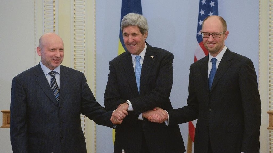U.S. Secretary of State John Kerry, center,  greets Ukrainian Prime Minister Arseniy Yatsenyuk, right, and parliament speaker Oleksandr Turchynov prior their meting in Kiev, Ukraine, Tuesday, March, 4, 2014.  In a somber show of U.S. support for Ukraine's new leadership, Secretary of State John Kerry walked the streets Tuesday where nearly 100 anti-government protesters were gunned down by police last month, and promised beseeching crowds that American aid is on the way.  The Obama administration announced a $1 billion energy subsidy package in Washington as Kerry was arriving in Kiev.( (AP Photo/Andrew Kravchenko, pool)