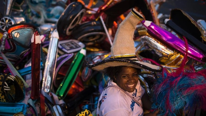 "Elaine da Silva Moraes poses for a photo backdropped by piles of discarded costumes after carnival celebrations at the Sambadrome in Rio de Janeiro, Brazil, Tuesday, March 4, 2014. Moraes is a ""catadora,"" or trash picker, and hundreds of others like her, for whom Carnival represents an annual boon. Dressed in a patchwork of costume parts rescued from the detritus, Moraes fills plastic garbage bags with her treasures - feathers, props, headgear and costly fabrics that she re-sells or transforms into new costumes or clothing.(AP Photo/Felipe Dana)"