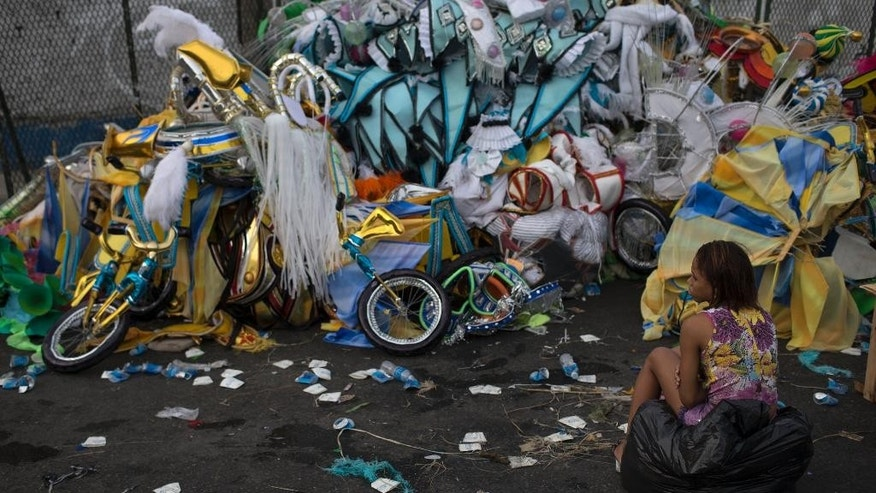 A woman sits in front of a pile of discarded carnival costumes after carnival celebrations at the Sambadrome in Rio de Janeiro, Brazil, Tuesday, March 4, 2014. The costumes on display at the all-night parade that ended early Tuesday have made Rioís Carnival celebration the most famous in the world. But the handmade confections often have a short shelf life. As the tens of thousands of revelers stream out of the Sambadrome, a surprising number of them immediately abandon their costumes. (AP Photo/Felipe Dana)