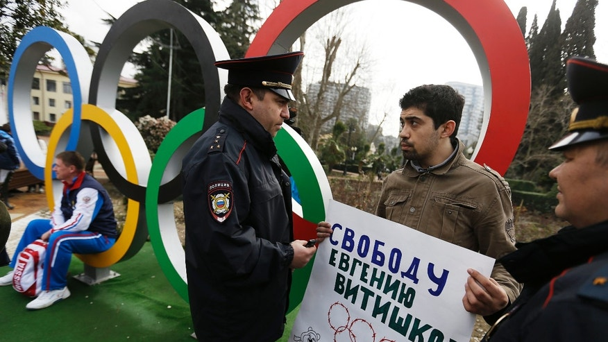 In this Monday Feb. 17, 2014 file photo, activist David Khakim, second right, is approached by two police officers after pulling out a banner protesting a recent prison sentence for a local environmentalist in front of the Olympic rings, in central Sochi, Russia. (AP Photo/David Goldman, file)