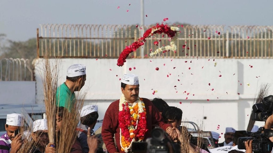 A supporter throws a floral garland at anti-graft activist and leader of Aam Aadmi Party, or Common Man Party, Arvind Kejriwal upon his arrival for a four-day visit of Gujarat state ahead of the country's national elections, in Ahmadabad, India, Wednesday, March 5, 2014. India said Wednesday it will begin national elections on April 7, kicking off a month-long contest in the largest democracy in the world. More than 810 million people are eligible to vote this year, an increase of 100 million from five years ago, according to the Election Commission. (AP Photo/Ajit Solanki)