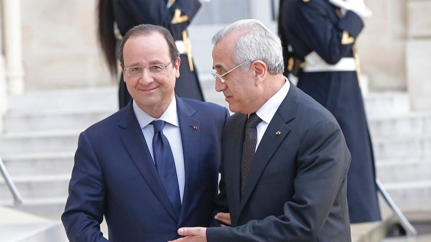 France's President Francois Hollande, left, welcomes Lebanon's President Michel Sleiman for a meeting of the International Support Group for Lebanon, at the Elysee Palace in Paris, Wednesday, March 5, 2014. (AP Photo/Michel Euler)