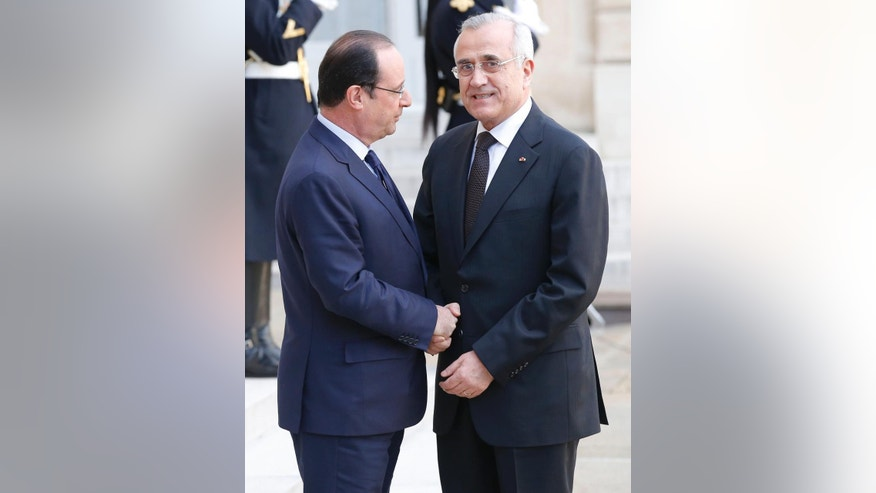 France's President Francois Hollande, left, welcomes Lebanon's President Michel Sleiman for a meeting of the International Support Group for Lebanon, at the Elysee Palace in Paris, Wednesday March 5, 2014. (AP Photo/Michel Euler)