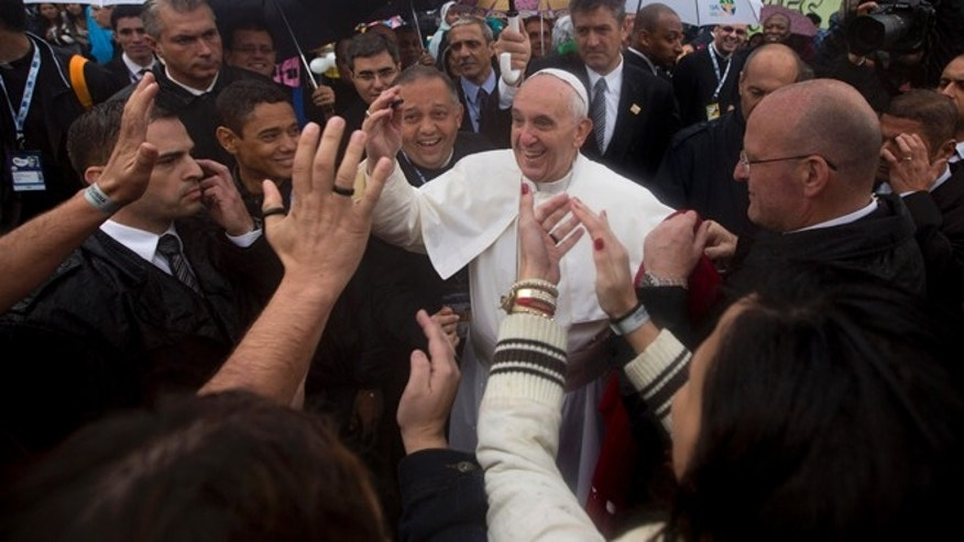 July 25, 2013: People greet Pope Francis, center, as he visits the Varginha slum in Rio de Janeiro, Brazil.