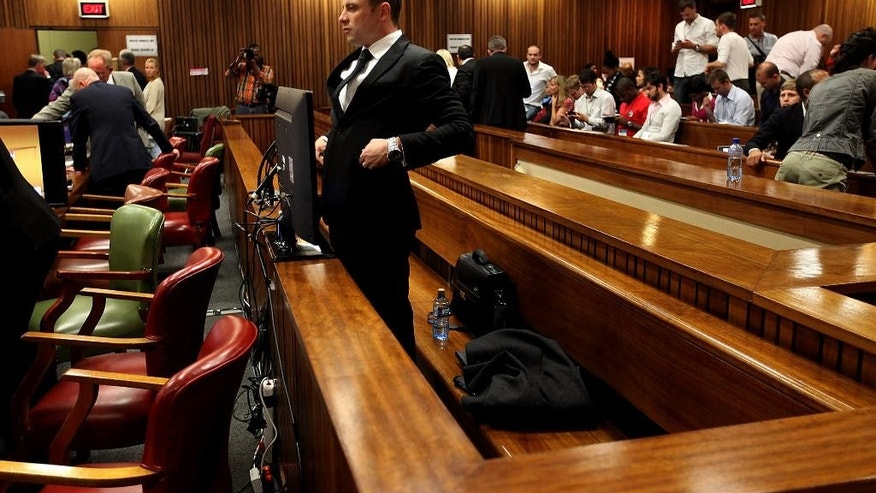 Oscar Pistorius stands in the dock on the third day of his trial at the high court in Pretoria, South Africa, Wednesday, March 5, 2014.  Pistorius is charged with murder for the shooting death of his girlfriend, Reeva Steenkamp, on Valentines Day in 2013. (AP Photo/Alon Skuy-Pool)