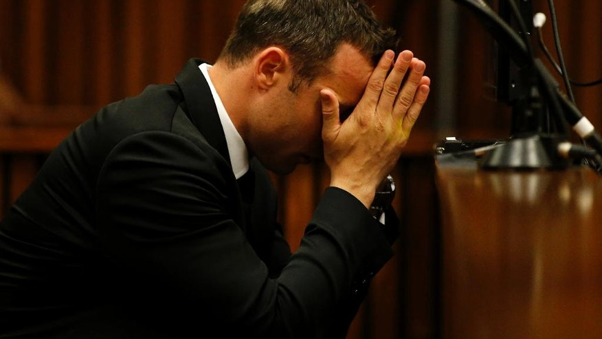 Oscar Pistorius sits in the dock in court on the third day of his trial at the high court in Pretoria, South Africa, Wednesday, March 5, 2014. Pistorius is charged with murder for the shooting death of his girlfriend, Reeva Steenkamp, on Valentines Day in 2013. (AP Photo/Siphiwe Sibeko, Pool)