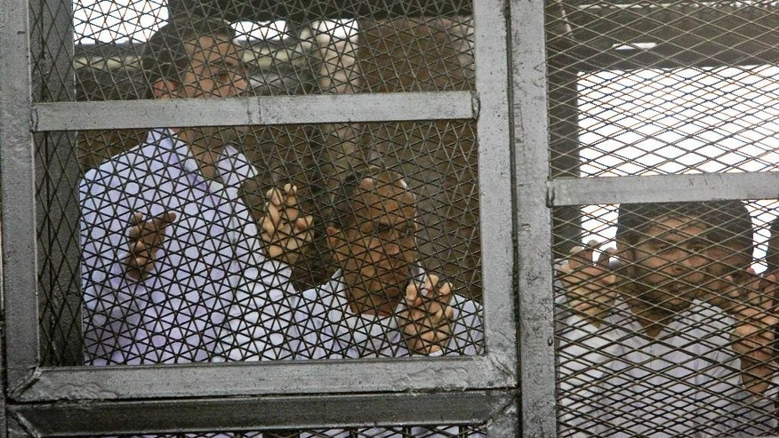 Al Jazeera producer Baher Mohamed, left, and correspondent Peter Greste, center, stand inside the defendants' cage in a courtroom during their trial on terror charges, along with several other defendants, in Cairo Egypt, Wednesday, March 5, 2014. (AP Photo/Mohammed Abu Zaid)