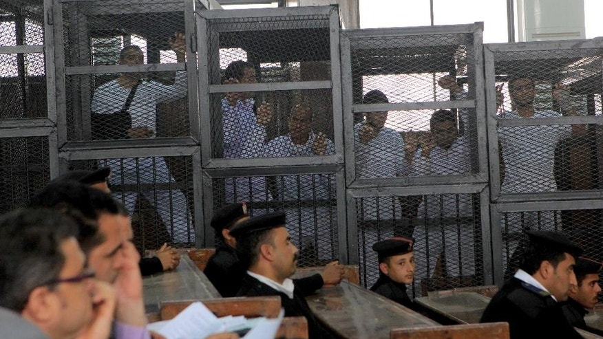 Al Jazeera English bureau chief Mohamed Fahmy, left, producer Baher Mohamed, second left, and correspondent Peter Greste, center, stand inside the defendants' cage in a courtroom during their trial on terror charges, along with several other defendants, in Cairo Egypt, Wednesday, March 5, 2014. (AP Photo/Mohammed Abu Zaid)