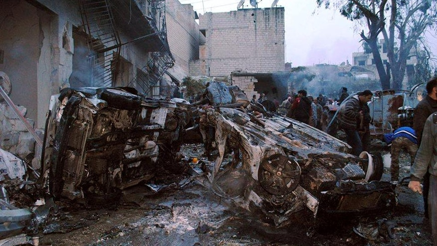 This picture taken on Saturday, March 1, 2014, provided by the anti-government activist group Coordination Committee In Kfar Takharim, which has been authenticated based on its contents and other AP reporting, shows Syrian citizens inspecting destroyed cars and buildings which were attacked by a Syrian government forces airstrike in the town of Kfar Takharim in the northwest province of Idlib, Syria. Government airstrikes hit residential buildings in the town of Kfar Tarakhim in the northwest province of Idlib on Saturday afternoon, according to the Idlib News group and the British-based Syrian Observatory for Human Rights. (AP Photo/Coordination Committee In Kfar Takharim)