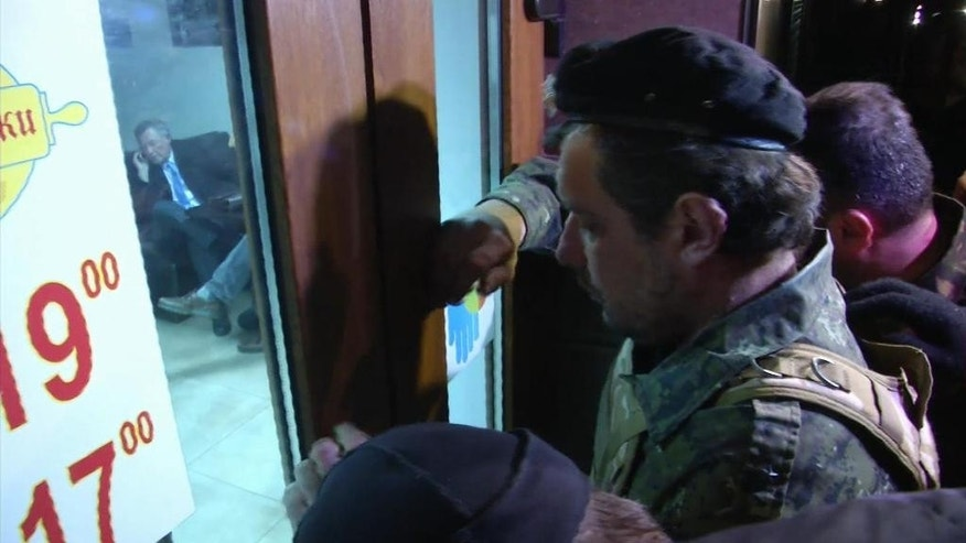 "This image taken from AP video shows a group of unidentified men in military fatigues outside a cafe in Simferopol, Ukraine who appear to be stopping UN Special Envoy to Ukraine, Robert Serry from leaving as he makes a call on his mobile phone inside, Wednesday, March 5, 2014. The special U.N. envoy who is visiting Crimea was threatened by 10 to 15 armed men on Wednesday and ordered to leave the region, where Ukraine and Russia are locked in a tense standoff, U.N. officials said. Later, an Associated Press reporter found Robert Serry in the business class lounge of the Simferopol airport on Wednesday evening. ""I'm safe. My visit was interrupted for reasons that I cannot understand,"" the Dutch diplomat said in a statement to AP. He said nothing more. (AP Photo/AP video)"