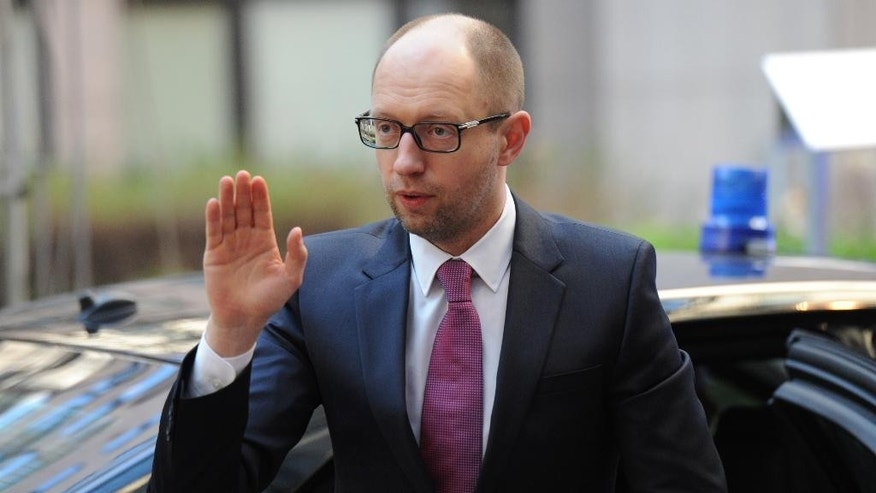 Ukraine's Prime Minister Arseniy Yatsenyuk waves as he arrives for an EU summit at the EU Council building in Brussels on Thursday, March 6, 2014. EU heads of state meet Thursday in emergency session to discuss the situation in Ukraine. (AP Photo/Geert Vanden Wijngaert)