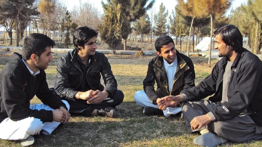 In this picture taken on Sunday, March 4, 2014, Afghan ex-translators for German military, Walid Shirzad, from left, Zamir Ahmadi, Atal Zafari and Shamsuddin Nawazish chat in a park during an interview with The Associated Press in Kunduz city, Afghanistan. According to the German government, about 950 Afghans have worked for Germany during the time its personnel have been present in Afghanistan, including drivers, translators and others. (AP Photo/Amad Yama)