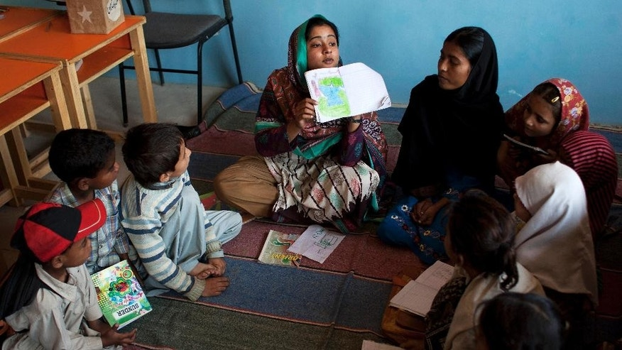 In this Monday, Feb. 24, 2014, Humaira Bachal, the founder of a charity school shows an illustration to students in Karachi, Pakistan. At the age of 13, Bachal began teaching other girls what she learned in school. Those classes at home between friends grew into her life's work: Bringing education to children in the working-class Muwach Goth neighborhood on the outskirts of Pakistan's port city of Karachi, where families often keep their girls out of school and where even boys struggle to get decent learning. (AP Photo/Shakil Adil)