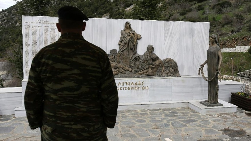 An army officer looks at the monument with the names of villagers who German army troops massacred, in the village of Ligiades near the northwestern town of Ioannina, Greece, on Thursday, March 6, 2014. German President Joachim Gauck's three-day visit to the country will include a speech Friday at the site where German army troops massacred 92 villagers near the northeastern town of Ioannina, and a meeting with the town's Jewish community. (AP Photo/Thanassis Stavrakis)