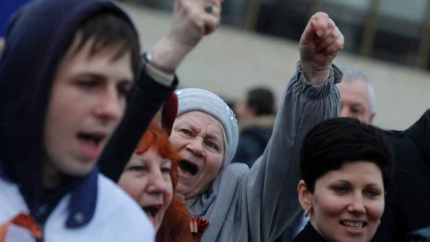 In this photo taken Wednesday, March 5, 2014, pro-Russian supporters chant slogans during a rally at a central square in Simferopol, Ukraine. Ukraine is facing a potentially crippling geographic and cultural divide, a growing gulf between supporters of Russia who dominate the east and south of the country, and western Ukrainians who yearn for closer ties to Western Europe.  One side of that divide is even starker in Crimea, a Black Sea peninsula. For much of the past 200 years, Crimea was under Russian and Soviet control, and today most Crimeans see themselves as only nominally Ukrainian and Russian is, by far, the dominant language (AP Photo/Sergei Grits)