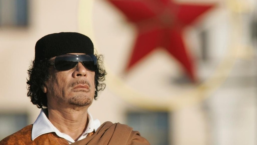 FILE - In this Monday, Nov. 3, 2008 file photo, Libyan leader Moammar Gadhafi attends a wreath laying ceremony in the Belarus capital Minsk. Gadhafi of nearly 42 years was captured by rebel forces in his hometown of Sirte in Oct. 2011. Libyan officials initially said Gadhafi was killed in crossfire between rebel fighters and loyalists. However, video footage emerged showing him being beaten, taunted and abused by his captors, raising questions about how and when he died. (AP Photo/Sergei Grits, File)