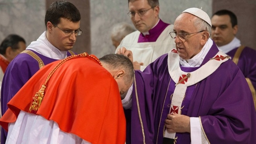 March 5, 2014: Pope Francis sprinkles with ashes a cardinal during the Ash Wednesday mass at the Santa Sabina Basilica in Rome.