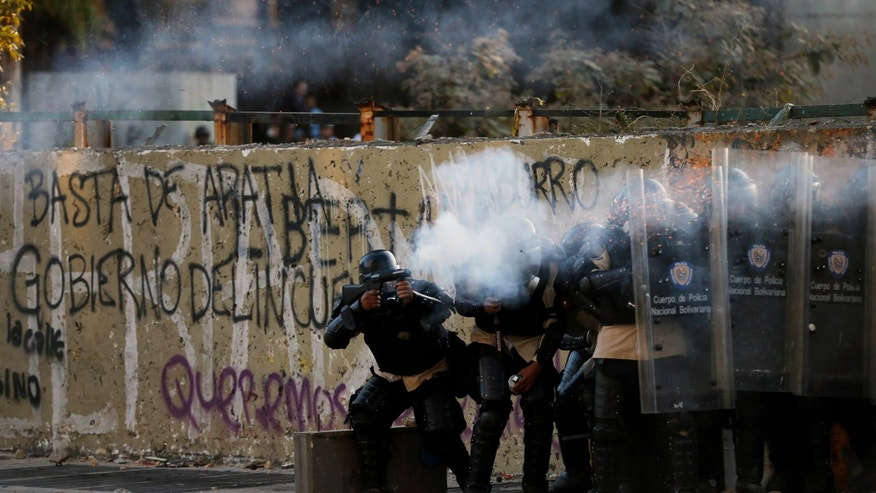 Police officers fire teargas at demonstrators  during clashes in Caracas, Venezuela, Wednesday, March 5, 2014.