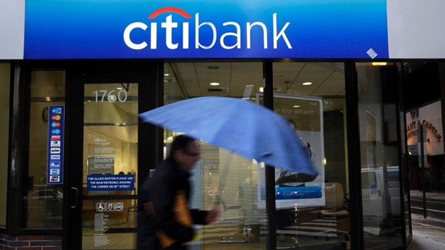 In this Jan. 14, 2014 file photo, a person walks past a Citibank location in Philadelphia. Citigroup reduced its 2013 earnings by $235 million on Friday, Feb. 28, 2014, saying it was a victim of fraud committed by a Mexican oil services company to secure hundreds of millions of dollars in short-term loans. (AP Photo/Matt Rourke, File)