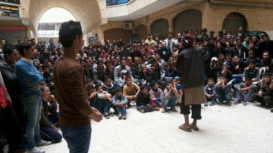 FILE - In this file picture released Thursday, Nov. 28, 2013, and posted on the Facebook page of a militant group, a member of the al-Qaida linked Islamic State of Iraq and the Levant (ISIL) gives a lecture at the Engineering College in the northern city of Raqqa, Syria. Once a vibrant, mixed city considered a bastion of support for President Bashar Assad, the eastern city of Raqqa is now a shell of its former life, transformed by al-Qaida militants into the nucleus of the terror group's version of an Islamic caliphate they hope one day to establish in Syria and Iraq. In rare interviews with The Associated Press, residents and activists in Raqqa describe a city where fear prevails, music has been banned, Christians have to pay religious tax in return for protection and face-veiled women and pistol-wielding men in jihadi uniforms patrol the streets. (AP Photo, File)
