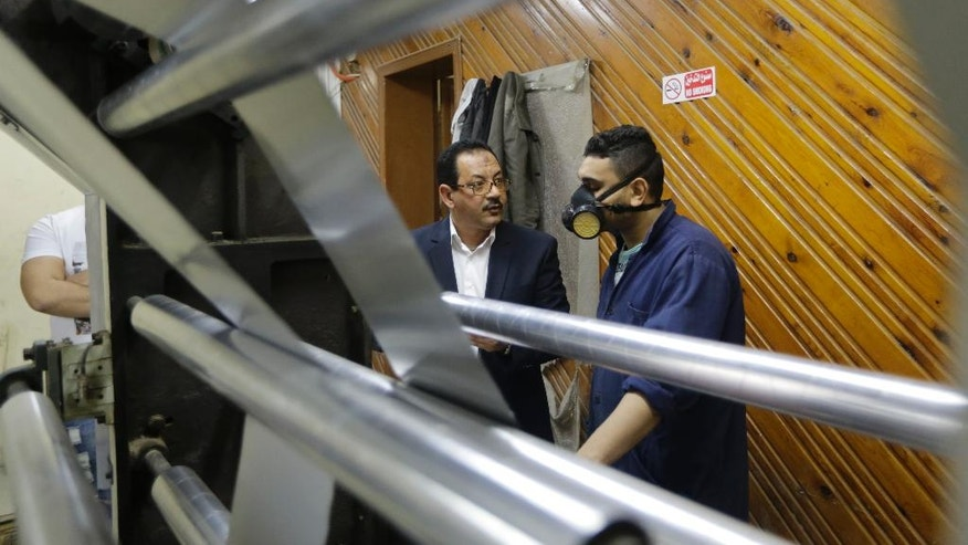 """In this Monday, March 3, 2014 photo, Adel Abd ElSadk, left, owner of the pharmaceutical packaging company Trustpack, talks with an employee manning one of the machines at his factory which has been financed in part by loans from the Social Development Fund, located just outside Cairo, Egypt. The program, called """"The Project"""" in Arabic, highlights entrepreneurship and small business acumen - something experts say is more crucial than ever as Egypt tries to claw its way out of tough economic times. (AP Photo/Amr Nabil)"""
