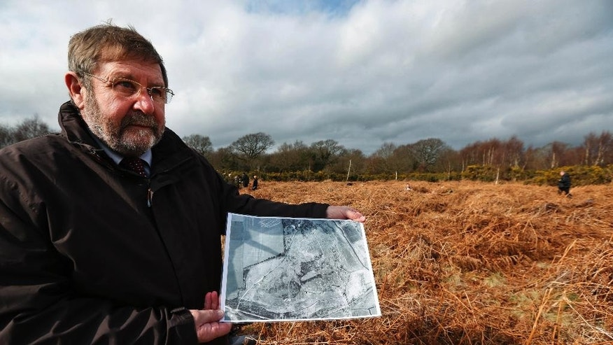 Councilor Graham Burgess of the local Hampsire council, holds a 1951 aerial photograph of the site, as he poses for the photographers at the site of WW1 practise trenches in Gosport, southern England, Thursday, March 6, 2014. This overgrown and oddly corrugated patch of heathland on England's south coast was once a practice battlefield, complete with trenches, weapons and barbed wire. Thousands of troops trained here to take on the Germany army. After the 1918 victory _ which cost 1 million Britons their lives _ the site was forgotten, until it was recently rediscovered by a local official with an interest in military history. Now the trenches are being used to reveal how the Great War transformed Britain _ physically as well as socially. As living memories of the conflict fade, historians hope these physical traces can help preserve the story of the war for future generations. (AP Photo/Lefteris Pitarakis)