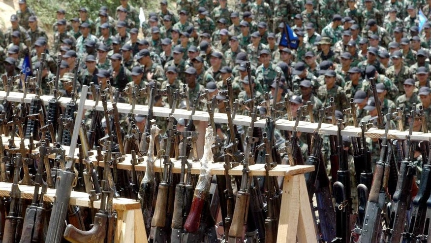 "FILE - In this Aug. 1, 2005 file photo, paramilitary fighters from the ""Heroes of Granada"" faction of the United Self-Defense Forces of Colombia, or AUC, attend a demobilization ceremony in Cristales, Colombia. Hundreds of right-wing paramilitaries are expected to walk free from prison beginning in March 2014 after serving eight-year sentences for crimes that normally carry more than triple the prison terms. Their lenient sentences were enshrined in a 2005 ""Justice and Peace"" law that provided a legal framework for the militias' supposed dismantling under a peace deal with the government of then-President Alvaro Uribe. (AP Photo/Luis Benavides, File)"