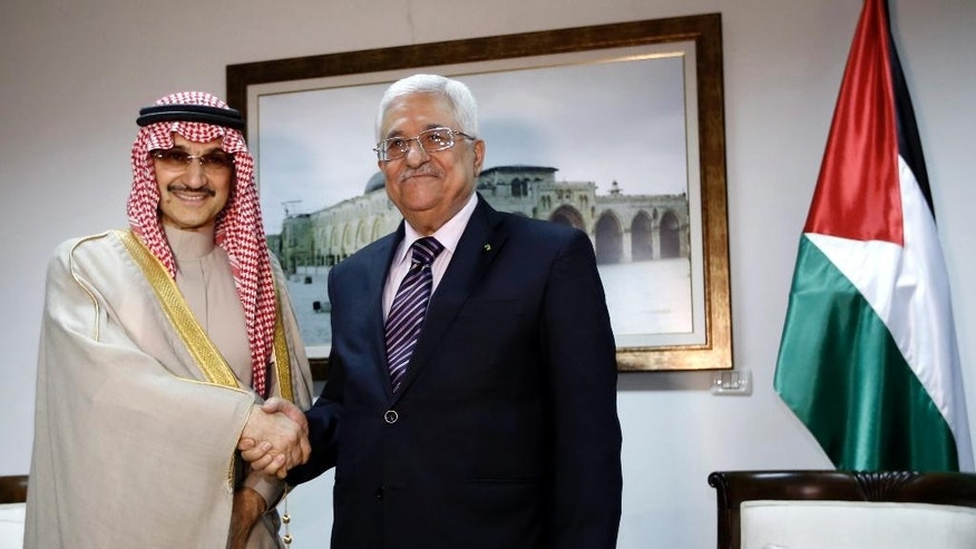 March 4, 2014 - Palestinian President Mahmoud Abbas, right, shakes hands with Saudi Prince Alwaleed bin Talal, during their meeting in the West Bank city of Ramallah.