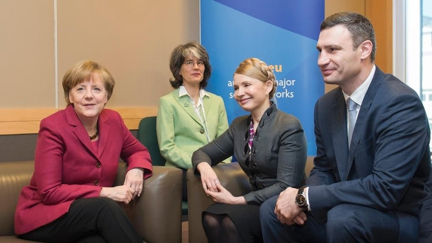 In this picture provided by the German government German Chancellor Angela Merkel, left, meets with Ukrainian politicians Yulia Tymoshenko. second right, and Vitali Klitschko, right, on the occasion of a meeting of the European peoples parties in Dublin, Ireland, Friday, March 7, 2014. Second left is an unidentified interpreter. (AP Photo/German Government/Guido Bergmann)