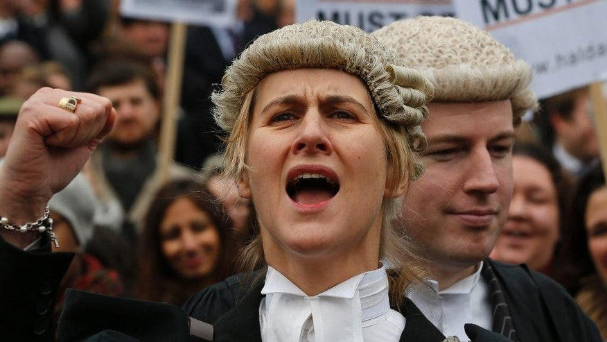 Barrister Juliet Donovan in her full court dress of wig and gown, chants slogans during a rally to protest against legal aid cuts, across from the Houses of Parliament in central London, Friday, March 7, 2014. The protest coincides with a nationwide demonstration of non-attendance of lawyers which will affect hundreds of cases across the country. (AP Photo/Lefteris Pitarakis)