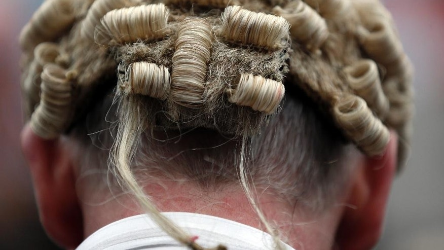 A lawyer in his full court dress of wig and gown, participates in a rally to protest against legal aid cuts, across from the Houses of Parliament in central London, Friday, March 7, 2014. The protest coincides with a nationwide demonstration of non-attendance of lawyers which will affect hundreds of cases across the country. (AP Photo/Lefteris Pitarakis)