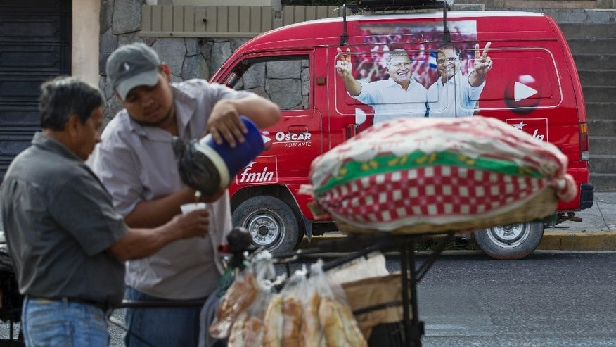 A man sells coffee in front of a car with electoral propaganda for the current Vice President and presidential candidate of the ruling Farabundo Marti National Liberation Front,  FMLN, Salvador Sanchez Ceren, in San Salvador, El Salvador, Thursday March. 6, 2014. El Salvador will hold a runoff election on March 9, between Sanchez Ceren and Norman Quijano, presidential candidate of the Nationalist Republican Alliance party, ARENA. (AP Photo/Esteban Felix)