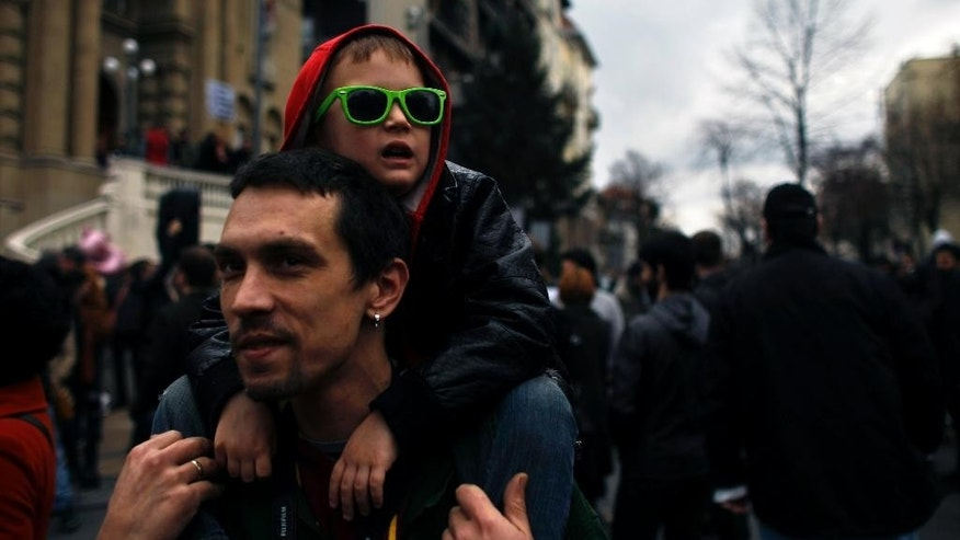A man carries a boy on his shoulders during a protest in front of the Nikola Tesla Museum in Belgrade, Serbia, Saturday, March 8, 2014.  Several hundred people are joining the dispute between the Serbian Orthodox Church and Serbia's nationalist authorities because of a bid to move the remains of visionary scientist Nikola Tesla from the Tesla Museum to a church in Belgrade. Famed Serbian scientific pioneer in electricity, radio and x-rays, died in 1943. (AP Photo/ Marko Drobnjakovic)