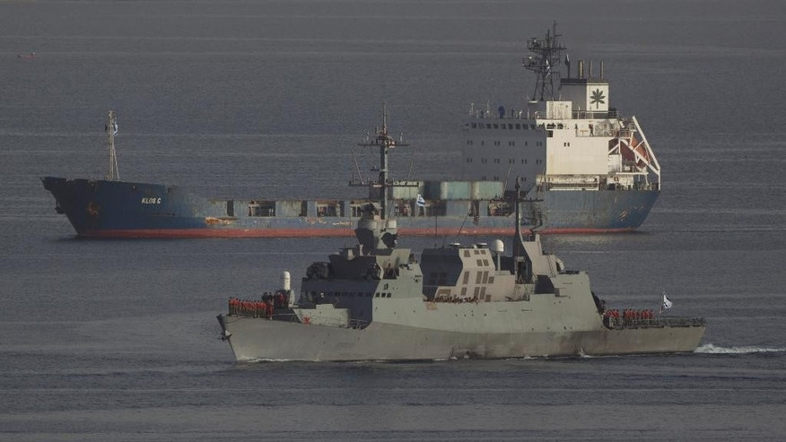 An Israeli naval warship escorts the seized Klos-C cargo ship as it enters the port at the Red Sea resort city of Eilat, southern Israel, Saturday, March 8, 2014.  Israeli naval forces raided the ship hundreds of miles from Israel, in the Red Sea on Wednesday and seized dozens of advanced rockets from Iran destined for Palestinian militants in Gaza, according to the Israeli military. The Islamic Jihad, an Iranian-backed militant group in the Gaza Strip, on Friday said it was not involved in a seized missile shipment.  (AP Photo/Ariel Schalit)