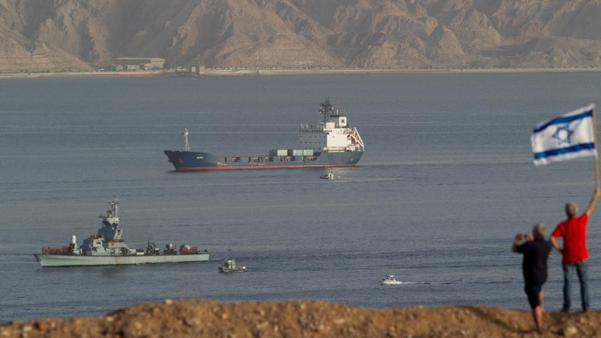 People wave an Israeli flag as the seized Klos-C cargo ship, accompanied by Israeli Naval vessels, approaches the port at the Red Sea resort city of Eilat, southern Israel, Saturday, March 8, 2014.  Israeli naval forces raided the ship hundreds of miles from Israel, in the Red Sea on Wednesday and seized dozens of advanced rockets from Iran destined for Palestinian militants in Gaza, according to the Israeli military. The Islamic Jihad, an Iranian-backed militant group in the Gaza Strip, on Friday said it was not involved in a seized missile shipment.  (AP Photo/Ariel Schalit)