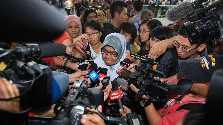 FILE - In this March 8, 2014 photo, a family member of passengers aboard a missing Malaysia Airlines plane is mobbed by journalists at Kuala Lumpur International Airport in Sepang, outside Kuala Lumpur, Malaysia. More than a day and a half has passed since the Boeing 777 jet disappeared from radar contact in the first hour of a six-hour flight from Kuala Lumpur, Malaysia to China's capital. From France to Australia and China, families and friends are enduring an agonizing wait for news about flight MH370. (AP Photo/Lai Seng Sin, File)