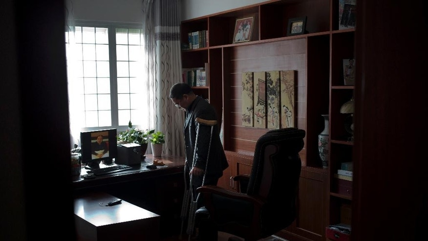 "In this Monday, Jan. 20, 2014 photo, Zhou Wangyan, head of the Liling city land resources bureau, uses crutches to stand near a computer displaying an image of him after his release from Communist Party detention in January 2013, during an interview at his home in Liling in central China's Hunan province. Zhou is one of four party members in Hunan who provided rare, on-the-record accounts of abuse they suffered in the party's secretive ""shuanggui"" detention system. (AP Photo/Andy Wong)"
