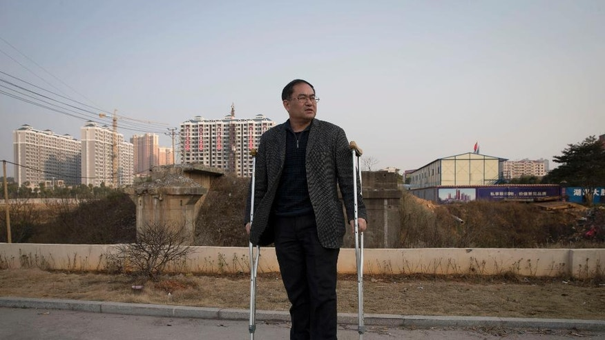 "In this Monday, Jan. 20, 2014 photo, Zhou Wangyan, head of the Liling city land resources bureau, stands with crutches near a plot of land under development in Liling city in central China's Hunan province. Zhou said he was detained by anti-corruption investigators for 184 days, deprived of sleep and food, nearly drowned, whipped with wire, forced to eat excrement, and that interrogators broke his left leg. ""It was a living hell,"" he said. ""It was worse than being a pig or a dog."" Local anti-graft officials on a Hunan online forum in February 2012 denied Zhou was tortured, saying he injured himself by slipping in the bathroom. (AP Photo/Andy Wong)"