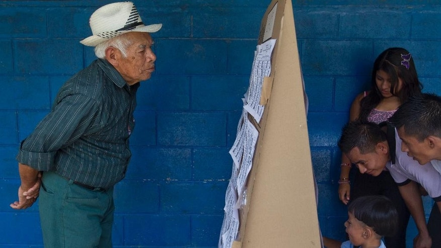 Voters search a list for the location of their respective polling tables during the presidential runoff election in Panchimalco, on the outskirts of San Salvador, El Salvador, Sunday, March 9, 2014. Salvadorans headed to the polls Sunday to elect their next president in a runoff between former Marxist guerrilla Salvador Sanchez Ceren from the ruling Farabundo Marti National Liberation Front (FMLN), and former San Salvador Mayor Norman Quijano from the Nationalist Republican Alliance (ARENA). (AP Photo/Esteban Felix)