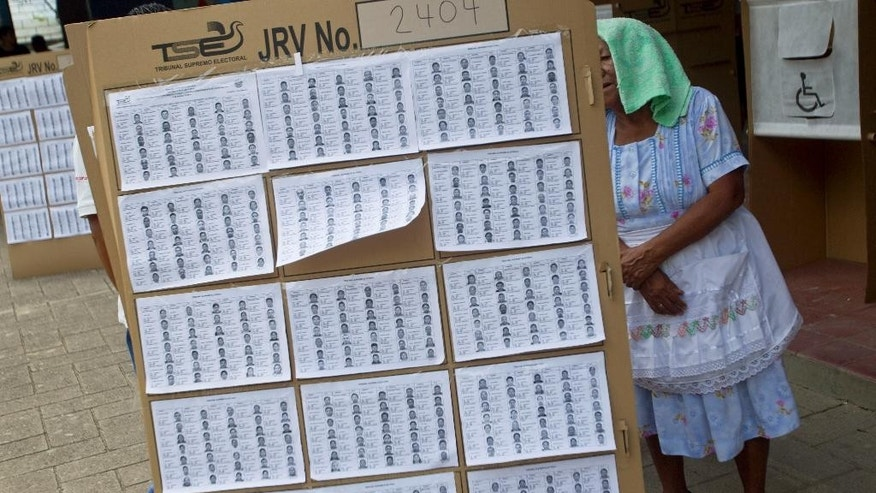 A voter searches a list for the location of her respective polling table during the presidential runoff election in Panchimalco, on the outskirts of San Salvador, El Salvador, Sunday, March 9, 2014. Salvadorans head to the polls Sunday to elect their next president in a runoff between former Marxist guerrilla Salvador Sanchez Ceren from the ruling Farabundo Marti National Liberation Front (FMLN), and former San Salvador Mayor Norman Quijano from the Nationalist Republican Alliance (ARENA). (AP Photo/Esteban Felix)