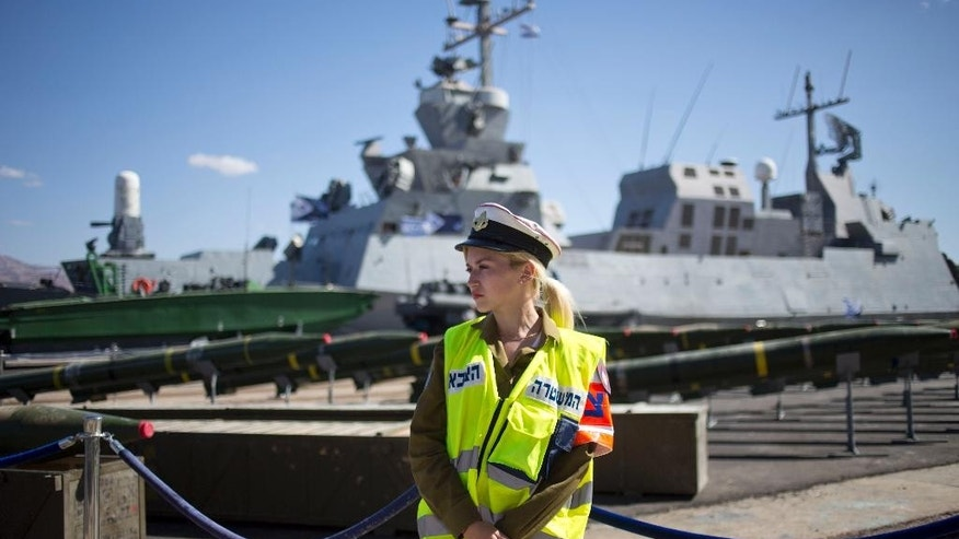 An Israeli military policewoman stands in front of a display of rockets seized from the Panama-flagged KLOS C civilian cargo ship that Israel intercepted last Wednesday, about 100 miles (160 kilometers) off the coast of Sudan, at a military port in the Red Sea city of Eilat, southern Israel, Monday, March 10, 2014. Israel has alleged the shipment was orchestrated by Iran and was intended for Islamic militants in Gaza, a claim denied by Iran and the rockets' purported recipients. Israel's military says the cargo ship carried 40 rockets with a range of up to 160 kilometers (100 miles) and dozens of mortar shells. (AP Photo/Ariel Schalit)