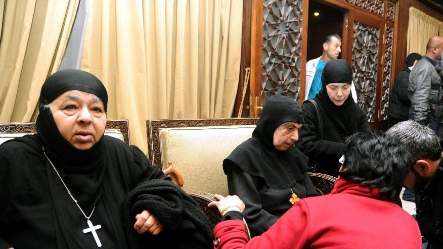 In this photo released by the Syrian official news agency SANA, a group of nuns, who were freed after being held by Syrian rebels, greet church officials at the Syrian border town of Jdeidat Yabous, early Monday, March. 10, 2014. Rebels in Syria freed more than a dozen Greek Orthodox nuns on Monday, ending their four-month captivity in exchange for Syrian authorities releasing dozens of female prisoners. The release of the nuns and their helpers, 16 women in all, is a rare successful prisoner-exchange deal between Syrian government authorities and the rebels seeking to overthrow the rule of President Bashar Assad. (AP Photo/SANA)