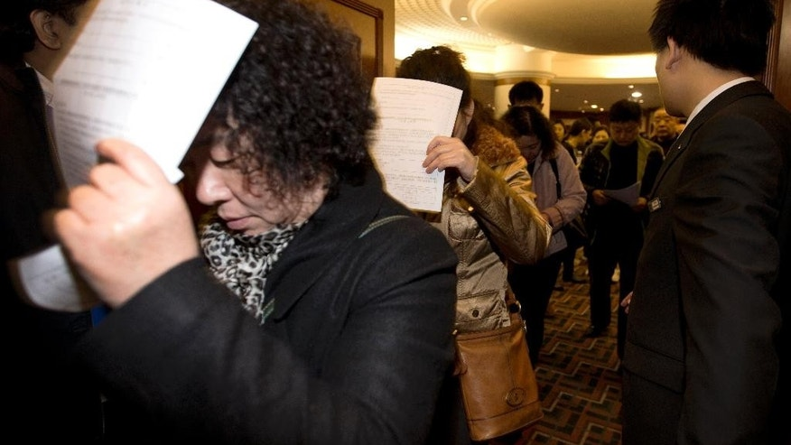 Chinese relatives of passengers aboard a missing Malaysia Airlines plane use application documents to block their faces as they walk out of a hotel room in Beijing Monday, March 10, 2014. The anguished hours had turned into a day and a half. Fed up with awaiting word on the missing plane, relatives of passengers in Beijing lashed out at the carrier with a handwritten ultimatum and an impromptu news conference. (AP Photo/Andy Wong)